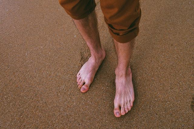 Muž v hnedých krátkych nohaviciach s bosými nohami stojí na piesku