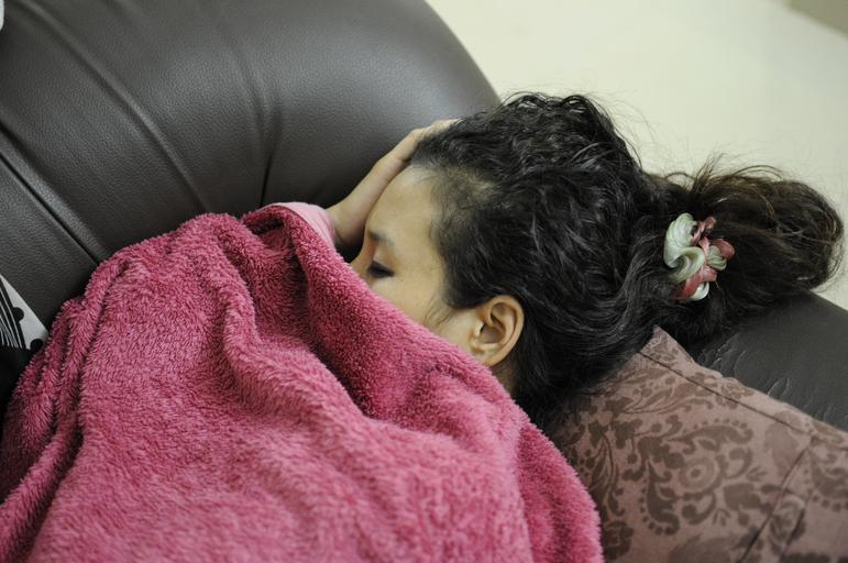 Žena spí prikrytá s dekou