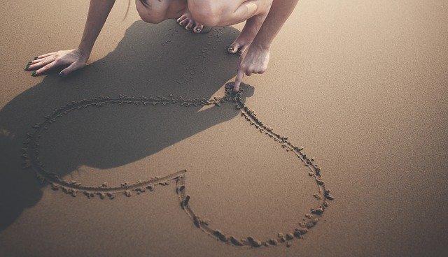 Žena kreslí srdce prstom do piesku na pláži.jpg