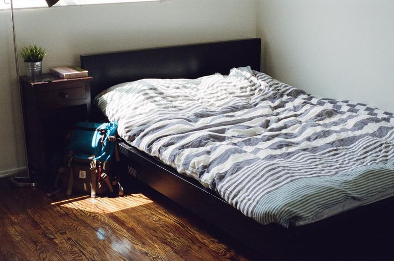 Izba s hnedou posteľou s bielymi obliečkami s pásikmi.jpg